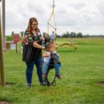 Woman pushing child on a swing that looks like a horse.