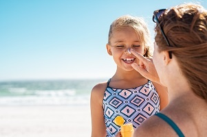 Mother applies sunscreen to daughter's face at the beach.