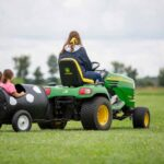Children in a wagon being pulled by someone on a lawn mower.