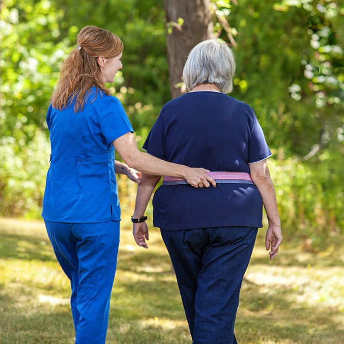 Ohioans HHC nurse helping patient walk.