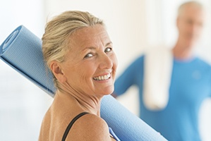 Older woman holding a yoga mat, looking back and smiling.