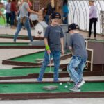Two boys playing putt-putt golf.